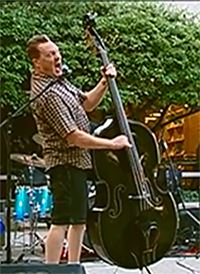 A man playing the upright bass and singing on stage.